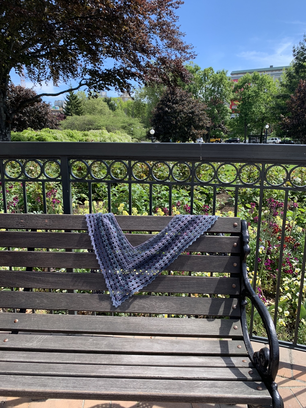 Scarf on bench with flowers in the background.